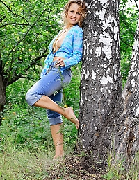 A cheerful Marusia  strikes a pose in the forest.